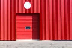 Rote Metalllagerwand mit geschlossenem Rollenfensterladentor lizenzfreie stockbilder