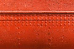 Rote Metallwandbeschaffenheit mit Nähten und Nieten Stockfoto