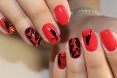Rote Nägel des Maniküredesigns mit Muster Stockfotos