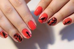 Rote Nägel des Maniküredesigns mit Muster Lizenzfreies Stockfoto