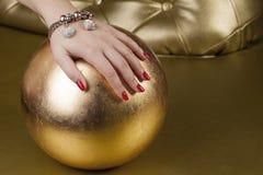 Rote Nagelhand auf einem goldenen Ball Stockfotos