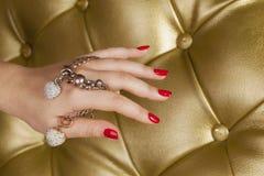 Rote Nagelhand mit einem Armband mit zwei Hirschen Lizenzfreies Stockbild