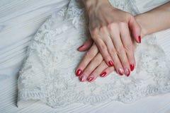 Rote Nagelkunst mit weißer Spitze mit Punkten und Linien Stockbilder