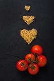 Rote neue Tomaten und Teigwarenherz formen schwarzes konkretes backgrou Lizenzfreie Stockfotos