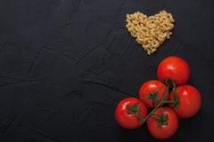 Rote neue Tomaten und Teigwarenherz formen schwarzes konkretes backgrou Lizenzfreie Stockbilder