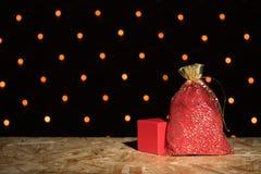 Rote neues Jahr ` s Tasche mit einem Geschenk und einem Kasten auf einem schwarzen Hintergrundesprit Lizenzfreie Stockfotografie