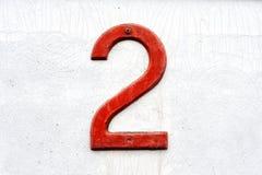 Rote Nr. 2 über verwittertem weißem Hintergrund stockbilder