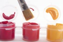 Rote orange Gelb-Acrylfarben und Malerpinsel Stockfoto