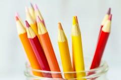 Rote orange Gelb-farbige Bleistifte im Glas Stockfoto