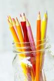 Rote orange Gelb-farbige Bleistifte im Glasgefäß Stockfotografie