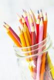 Rote orange Gelb-farbige Bleistifte im Glasgefäß auf Weiß Stockbilder