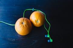 Rote Orangen und Kopfhörer lizenzfreies stockfoto