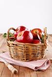 Rote organische Äpfel in einem Strohkorb auf hölzernem Hintergrund Stockfotos