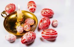 Rote Ostereier mit weißem Volksmuster auf Kerzenständer mit brennender Kerze in der linken Seite auf weißem Hintergrund Ukrainisc Lizenzfreies Stockfoto