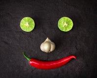 Rote Paprika-, Knoblauch- und Kalkzitrone vereinbaren als lächelndes Gesicht auf bla Stockbilder