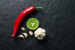 Rote Paprika-, Knoblauch- und Kalkzitrone vereinbaren auf schwarzem Stein-backgro Lizenzfreie Stockfotos