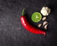 Rote Paprika-, Knoblauch- und Kalkzitrone vereinbaren auf schwarzem Stein-backgro Lizenzfreies Stockfoto