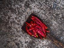 Rote Paprikas auf hölzernem Löffel Stockfotografie