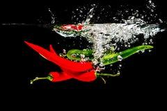 Rote Paprikas im Wasser Stockfotografie