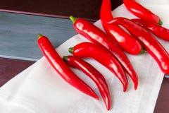 Rote Paprikas pepers an der weißen Serviette am bunten hölzernen Hintergrund Stockbilder