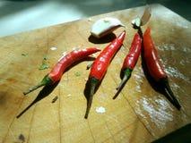 Rote Paprikas und Knoblauch auf hölzerner Ausschnittplatte Lizenzfreie Stockfotos