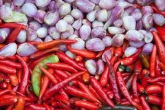 Rote Paprikas und rosa Zwiebelhintergrund Lizenzfreies Stockfoto
