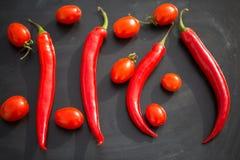 Rote Pepperonis und Tomaten auf einem hölzernen Hintergrund Lizenzfreie Stockbilder