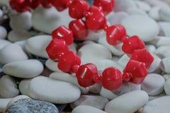 Rote Perlen auf Kieseln Stockbild