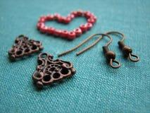 Rote Perlen in der Form des Herzens, Ohrringe herstellend, handgemachter Schmuck Lizenzfreies Stockbild