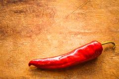 Rote Pfeffer auf altem Holztisch Lizenzfreie Stockfotos