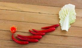 Rote Pfeffer und Kopfsalat Corlor auf einer hölzernen Platte Stockfotografie