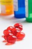 Rote Pillen und Verordnungflaschen Lizenzfreie Stockfotos