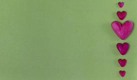 Rote Plasticineherzen auf einem hellgrünen Hintergrund Stockbilder
