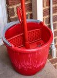 Rote Plastik-buicket und Moppeinstellung auf alter hinterer Veranda der haus- Nahaufnahme des Ziegelsteines stockfotos