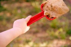 Rote Plastik- Schaufelschaufel in einer Kind-` s Hand Spiel im sandbo Stockfotografie