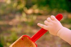 Rote Plastik- Schaufelschaufel in einer Kind-` s Hand Spiel im Sandkasten Mit einer Schaufel von Sandfällen Symbol der Kindheit u Lizenzfreies Stockfoto