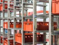 Rote Plastikkästen in den Zellen des automatisierten Lagers Stockfotos