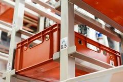 Rote Plastikkästen in den Zellen des automatisierten Lagers Lizenzfreie Stockfotos