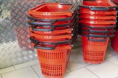 Rote Plastikkörbe für Waren vor einem Eingang Lizenzfreies Stockfoto