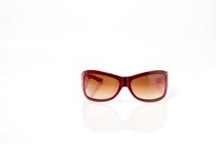 Rote Plastiksonnenbrillen mit brauner Linse Stockbilder