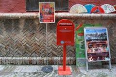 Rote Postbox- und Touristenanzeige am Souvenirladen Stockbild