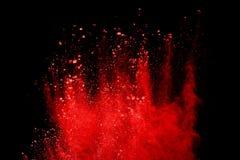 Rote Pulverexplosion lokalisiert auf schwarzem Hintergrund stockbild