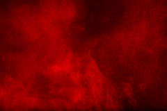 Rote Pulverwolke gegen dunklen Hintergrund stockfotos