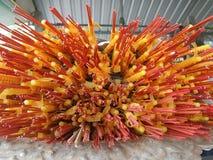 Rote Räucherstäbchen und gelbe Kerzen in einem buddhistischen Tempel Stockfotos