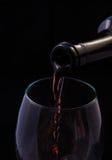 Rote Rebe, die aus Flasche gießt Lizenzfreies Stockfoto
