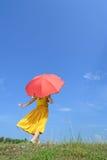 Rote Regenschirmfrauenstellung und Wolkenhimmel Stockfotografie