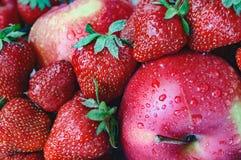 Rote reife Erdbeere und Apfel mit Wassertropfen Lizenzfreie Stockfotos