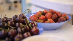Rote reife Erdbeeren in der Glasschüssel nahe der Kirsche rollen auf gestrickter Serviette auf der grauen Tabelle stock video