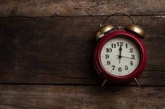 Rote Retro- Alarmglockeuhr auf alten Holzverkleidungen Stockfotos