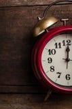 Rote Retro- Alarmglockeuhr auf alten Holzverkleidungen Stockfotografie